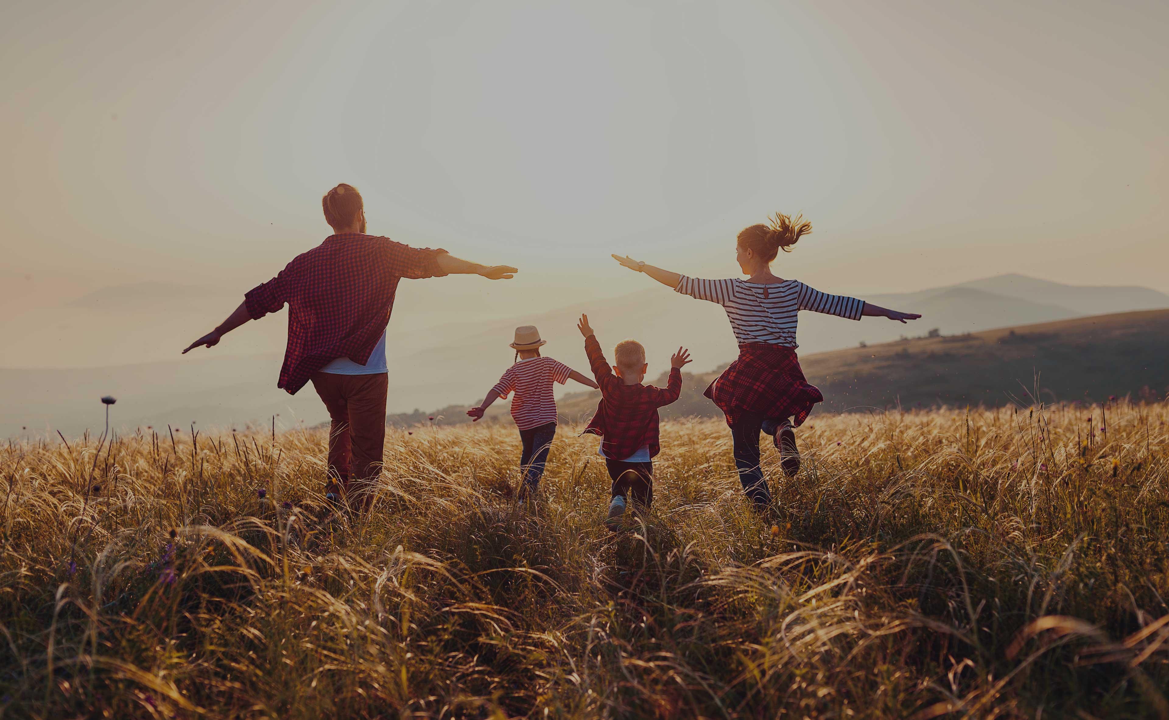 Familie laeuft mit ausgebreiteten Armen ueber Wiese
