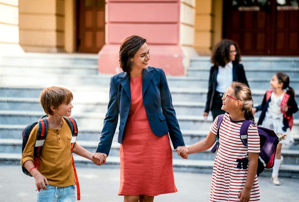 Mutter holt Kinder von der Schule ab