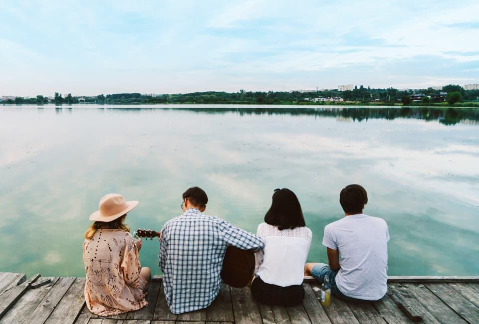 Junge Leute sitzen auf Steg und blicken auf Wasser