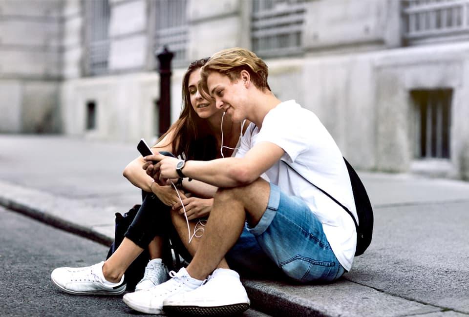 Junges Pärchen sitzt auf Bürgersteig und hört Musik