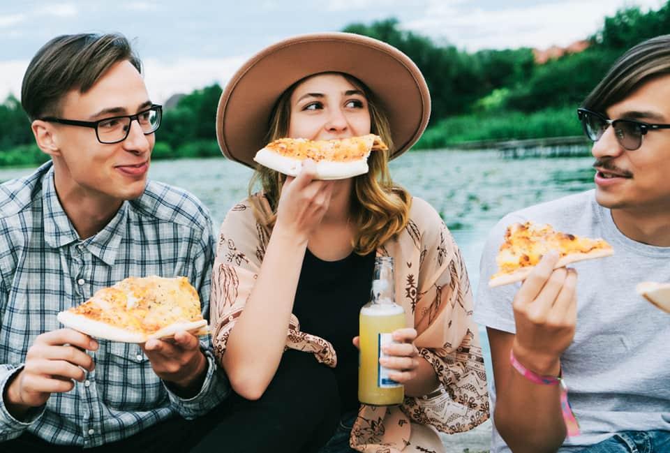 Junge Leute sitzen am Wasser und essen