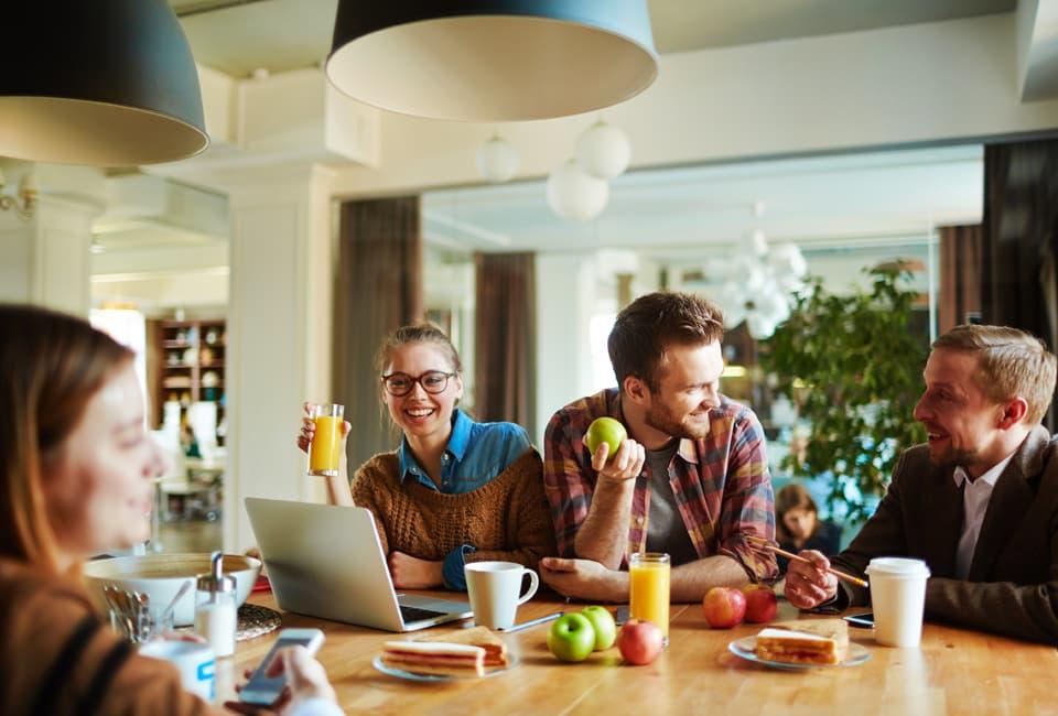 Junge Leute sitzen am Tisch und essen