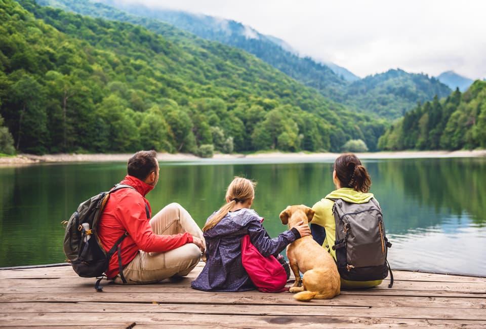 Familie sitzt am See in den Bergen