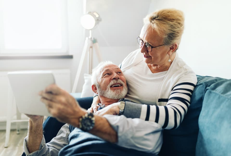 Älteres Paar sitzt auf der Couch