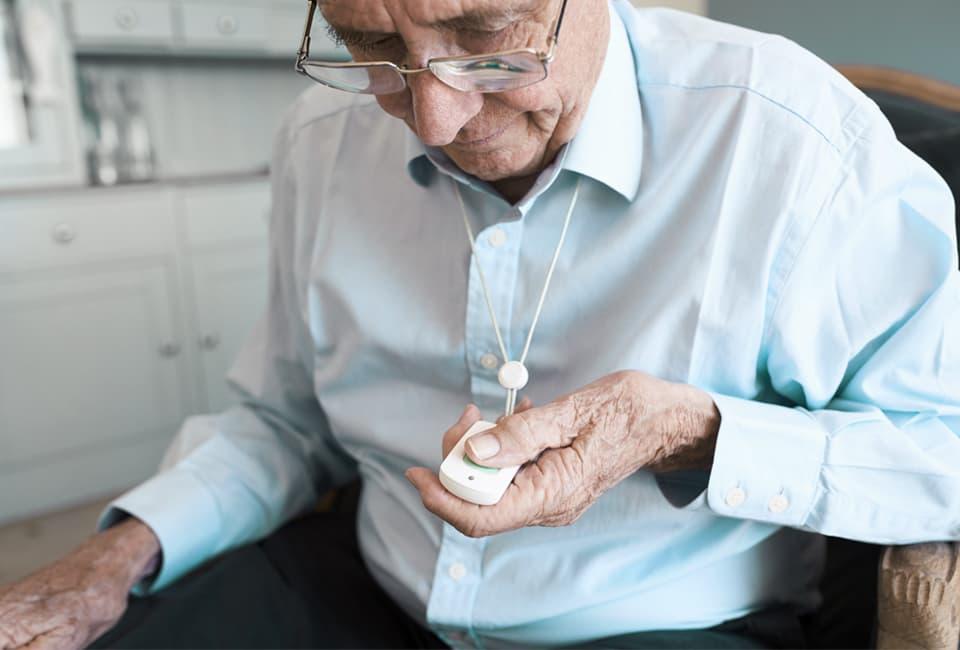 Älterer Mann mit Notrufknopf