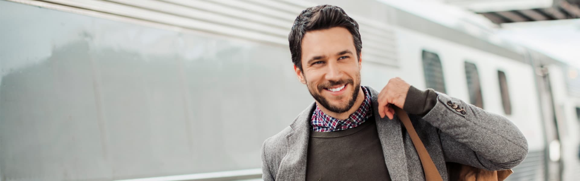 Lächelnder Mann im Tweed-Anzug am Bahngleis vor einem Zug