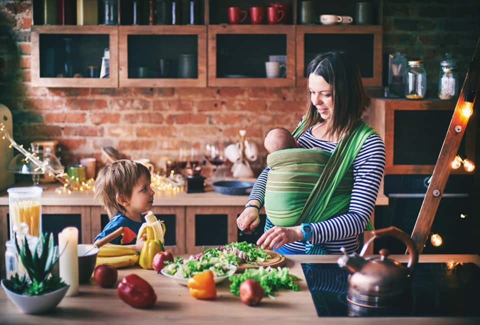 Mutter mit zwei Kindern beim Kochen