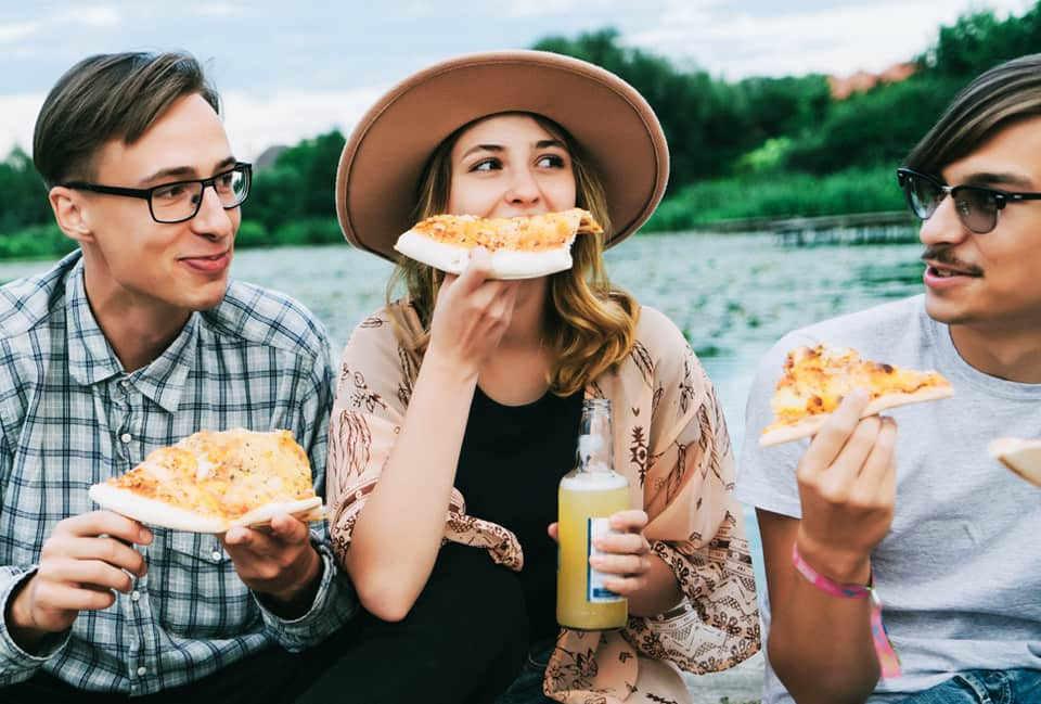 Junge Leute sitzen am Wasser und essen Pizza