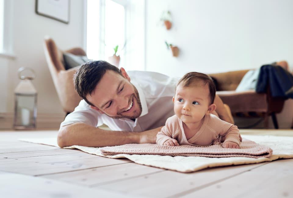 Junger Mann und Baby spielen auf dem Boden