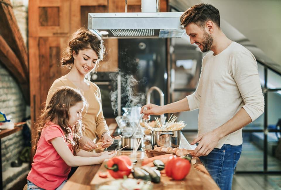 Junge Eltern und Mädchen beim Kochen