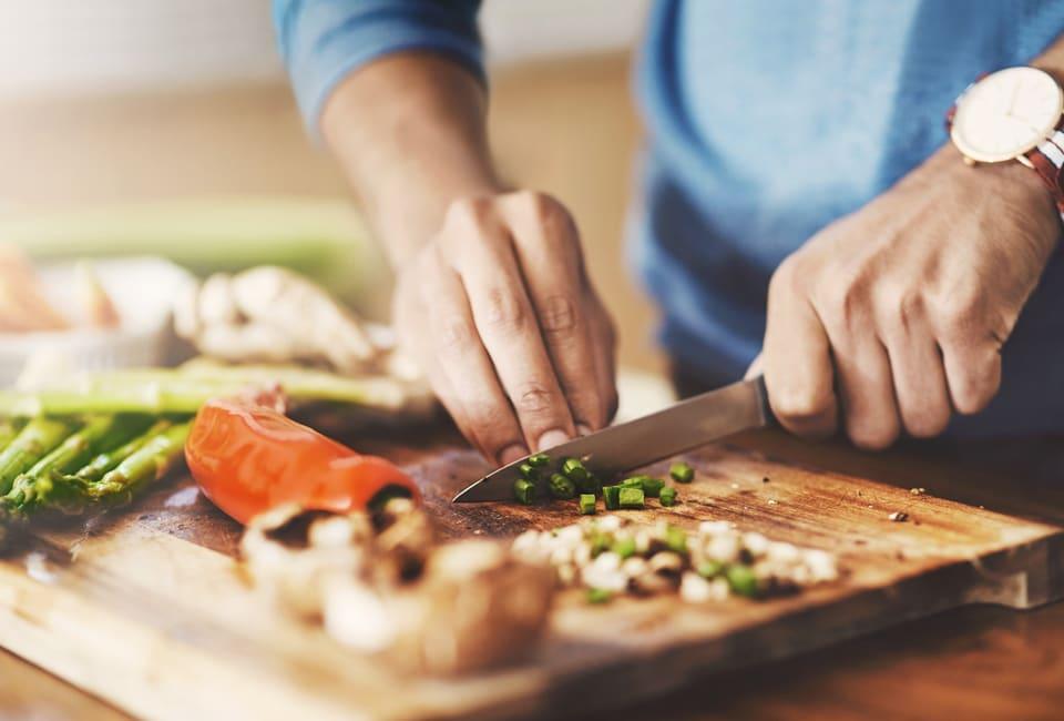 Hände schneiden auf Holzbrett Gemüse