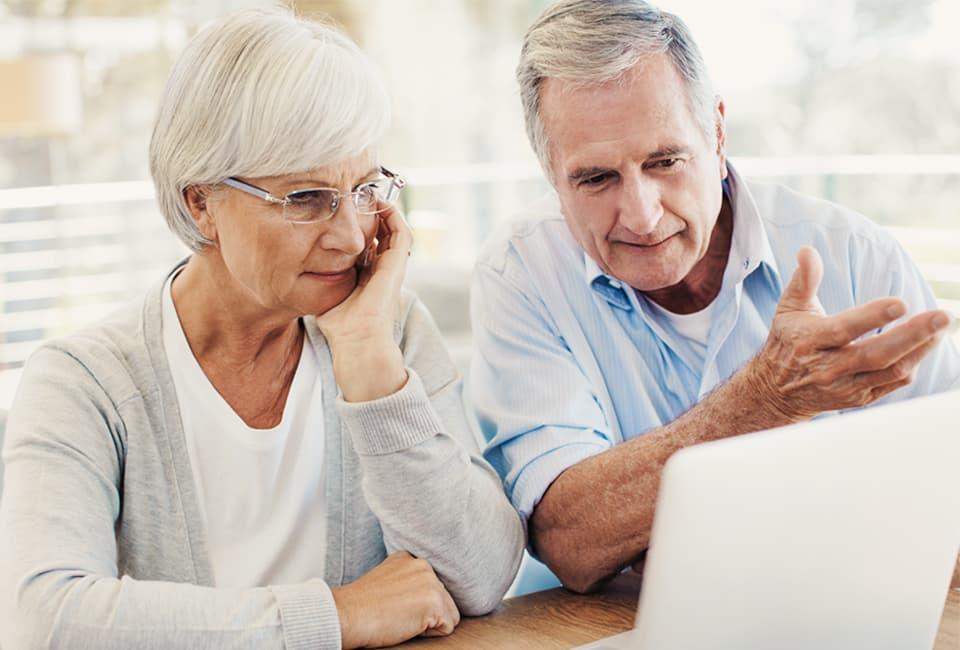Aeltere Frau und aelterer Mann am sitzen vor Laptop