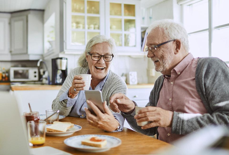 Aelteres Paar am Kuechentisch schauen auf Smartphone