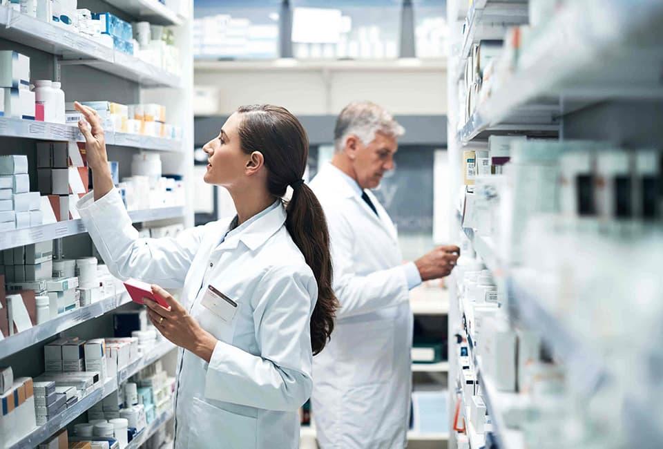 Apothekerin und Apotheker suchen das richtige Medikament