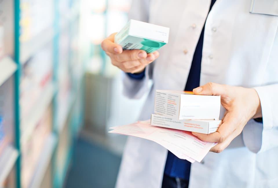 Apothekerin mit verschiedenen Medikamenten und Rezepten