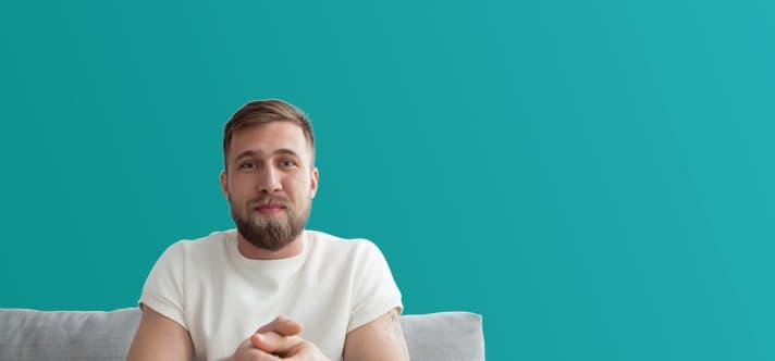 Lächelnder junger Mann sitzt auf einem Sofa