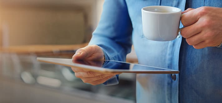 Mann im Jeans-Hemd hält in einer Hand eine Kaffeetasse und in der anderen ein Tablet